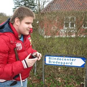 Blind mand med stok under armen står foran skilt til Blindecenter Bredegaard