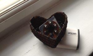 batterier til høreapperat ligge ri lille hjerteformet kurv. Ved siden af en høreapparatsæske fra Oticon