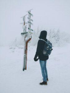 en perosn i sne står ved vejskilt