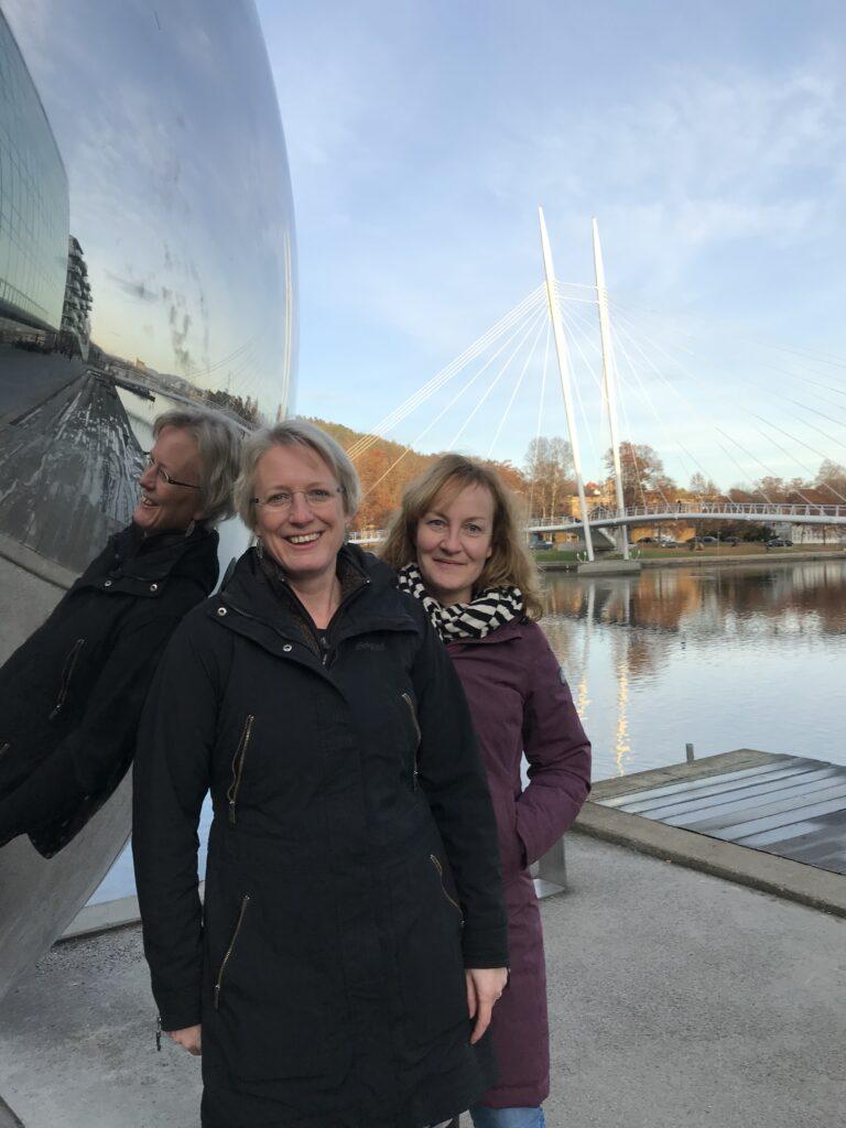 Rikke og Karin står foran skulptur, der spejler Rikke, vand og kaj.
